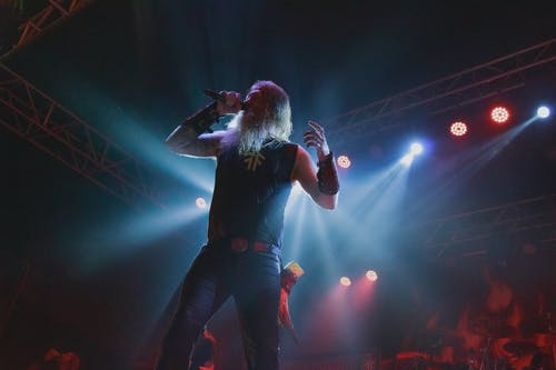 Man in Black Shirt and Blue Denim Jeans Singing on Stage