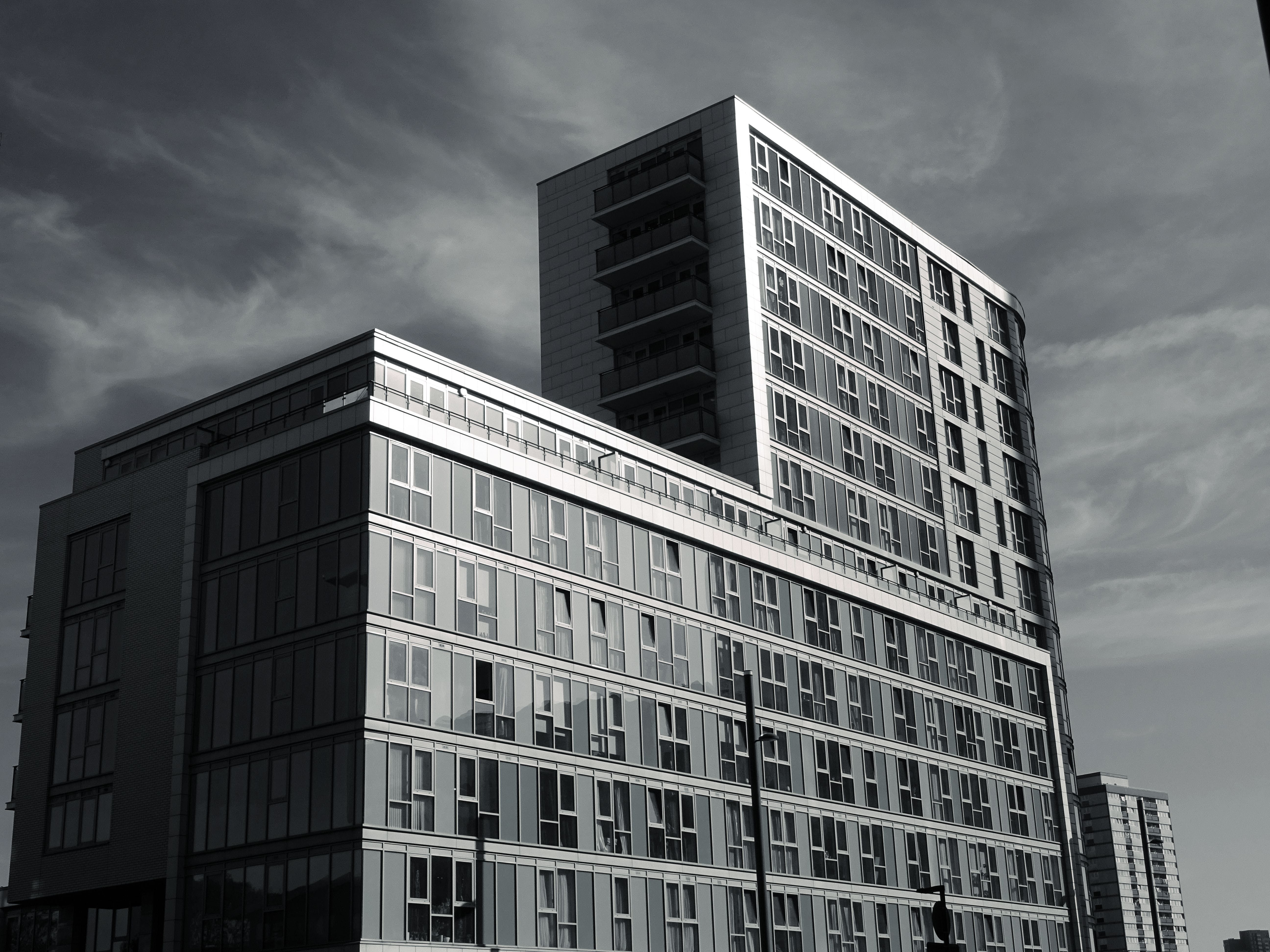 Grayscale Photo of Building Under Cloudy Day Sky
