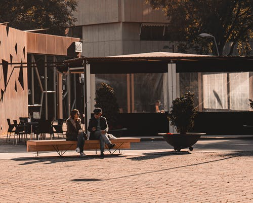 People resting and talking on bench
