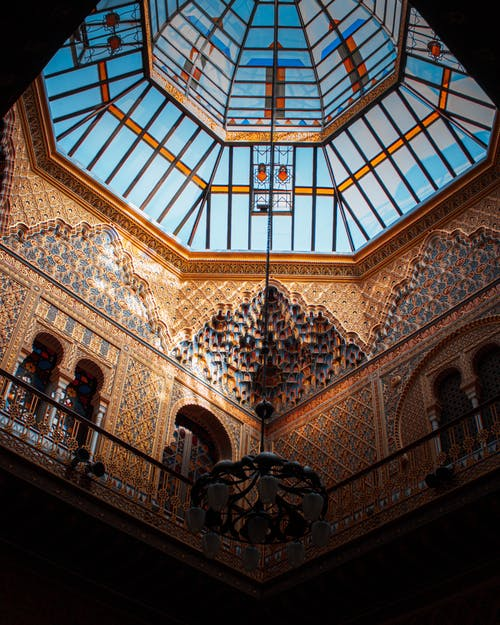 From below lamp hanging in stained glass dome inside of building decorated with traditional oriental ornaments