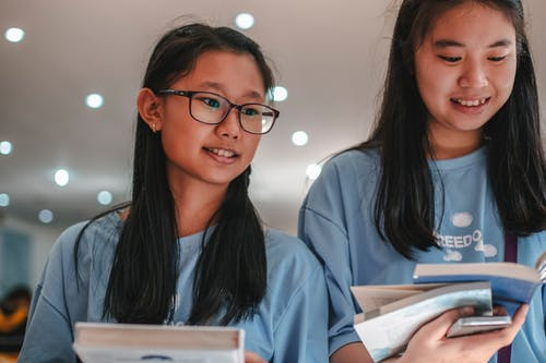 Girls Wearing Blue Shirt Looking at the Books