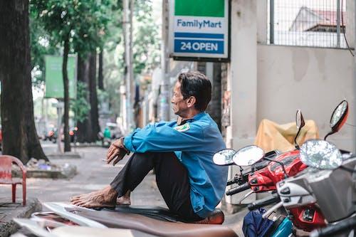 Man in Blue Dress Shirt Sitting on Sidewalk