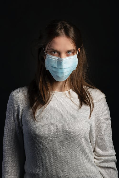 Woman in White Sweater Wearing Blue Face Mask