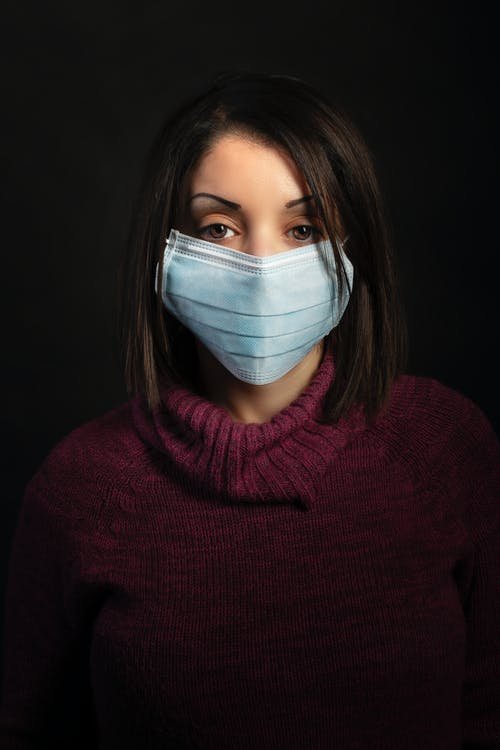 Woman in Purple Turtleneck Sweater With White Face Mask