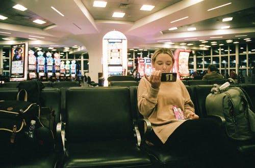 Free stock photo of airport, gambling machines, lady on her phone