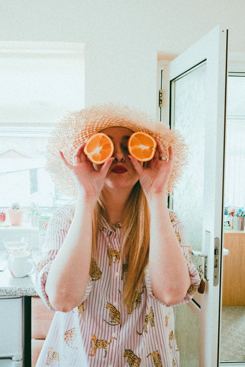 Woman in White Knit Sweater Holding Orange Round Sunglasses