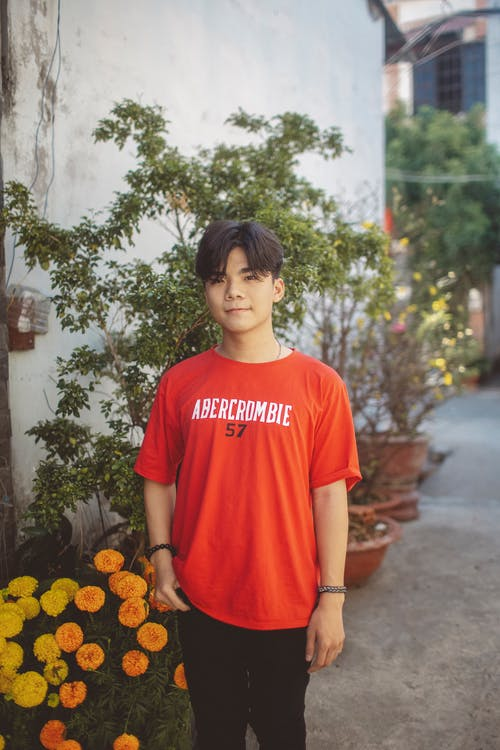 Boy in Red Crew Neck T-shirt Standing Near White Wall