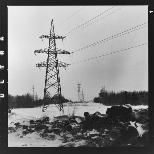 Grayscale Photo of Electric Tower
