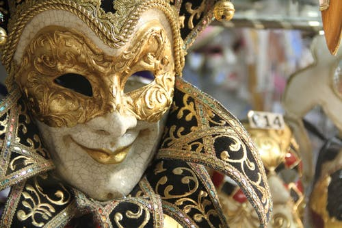 Closeup traditional elegant Venetian mask with golden ornaments hanging in vitrine of shop during carnival
