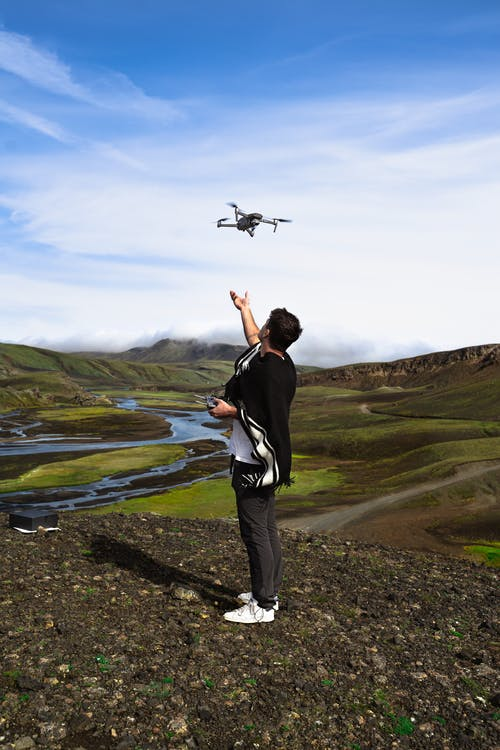 Man in Black Jacket and Gray Pants Standing on Green Grass Field Flying Drone