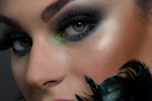 Closeup beautiful young woman with colorful eyeshadows and long eyelashes looking at camera