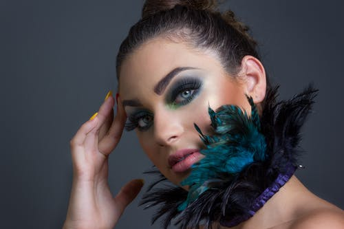 Attractive woman with feathers on neck