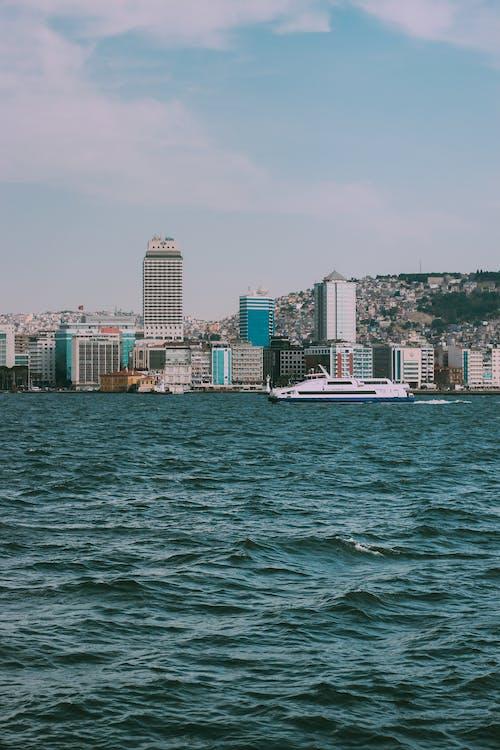 White Boat on Sea Near City Buildings