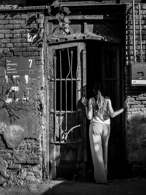 Woman in White Tank Top and White Pants Standing on the Door