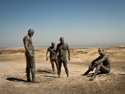 Men Covered in Mud Standing on Brown Sand