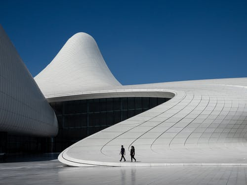 Distant man and woman walking outside futuristic geometric building against cloudless blue sky