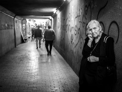 Sad elderly woman standing in passage