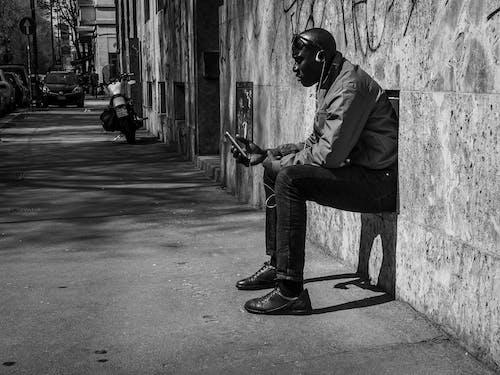 Black man listening to music on street