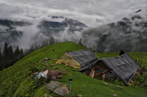 Green Grass Field With Tent on Top of Mountain