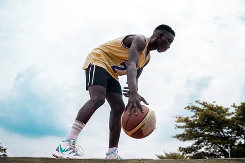 Man in Yellow Jersey Shirt and Black Shorts Holding Basketball