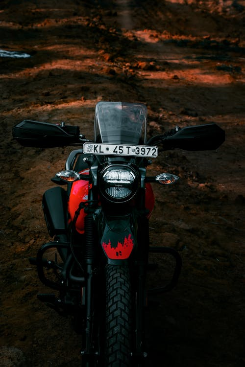 Black and Red Motorcycle Parked on Dirt Road