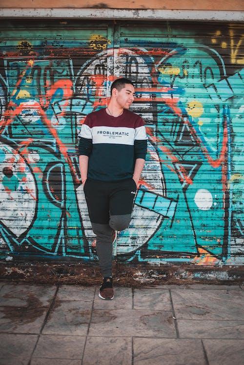 Man Leaning on Graffiti Wall