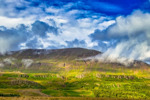 Green Grass Field Near Mountain Under White Clouds and Blue Sky