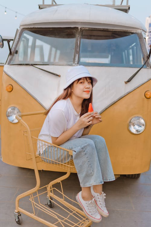 Woman in White Shirt and Blue Denim Skirt Sitting on Yellow Cart