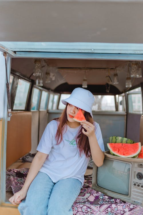 Woman in White Crew Neck T-shirt and White Cap Sitting Inside the Van