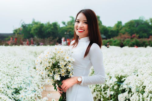 Delighted young Asian female in white dress holding bouquet of fresh flowers and smiling for camera on summer day in field