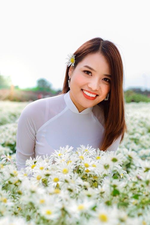Cheerful ethnic woman in flower field