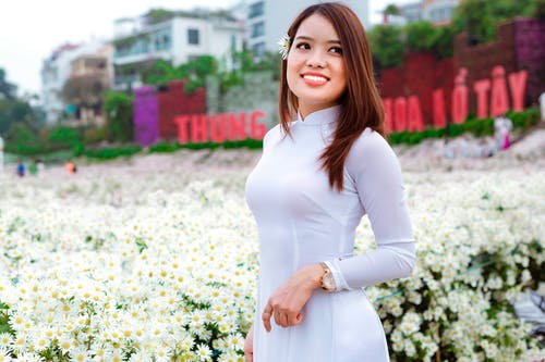 Glad Asian female in white dress smiling and looking away over shoulder while standing near white flowers on summer day