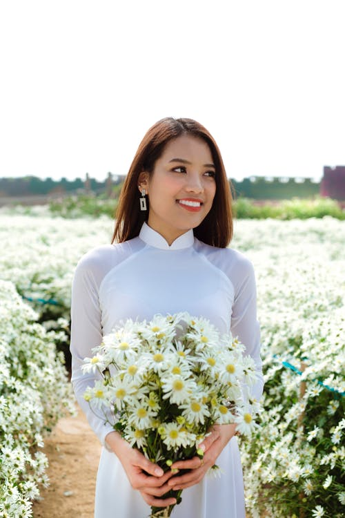 Happy young ethnic female with bunch of fresh flowers smiling and looking away while standing on path in field