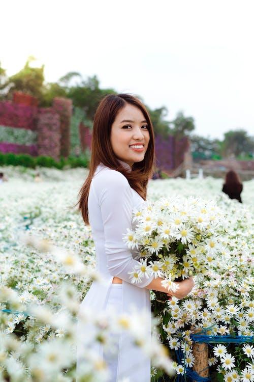 Happy ethnic female near flowers in garden