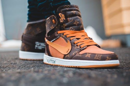 Person Wearing Brown Nike Air Jordan 1 Shoes