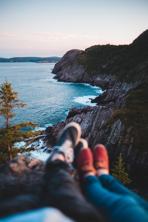 Crop couple resting on cliff near sea