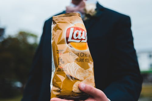 Unrecognizable man with bag of chips