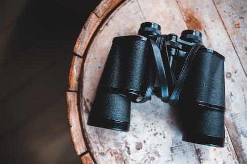 Black Binoculars on Brown Wooden Table