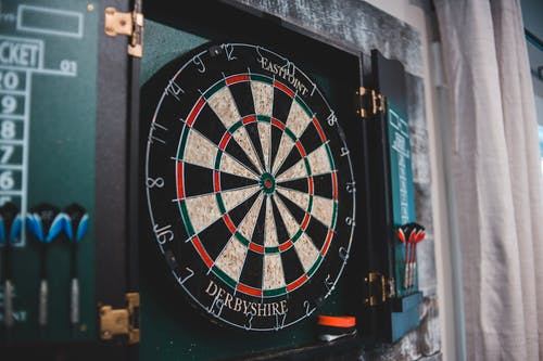 Round dartboard ready for game hanging on wall in cozy room at home