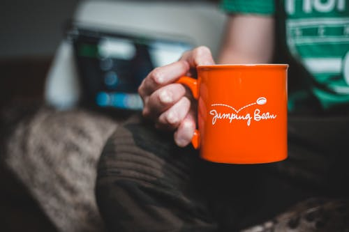 Person Holding Orange Ceramic Mug