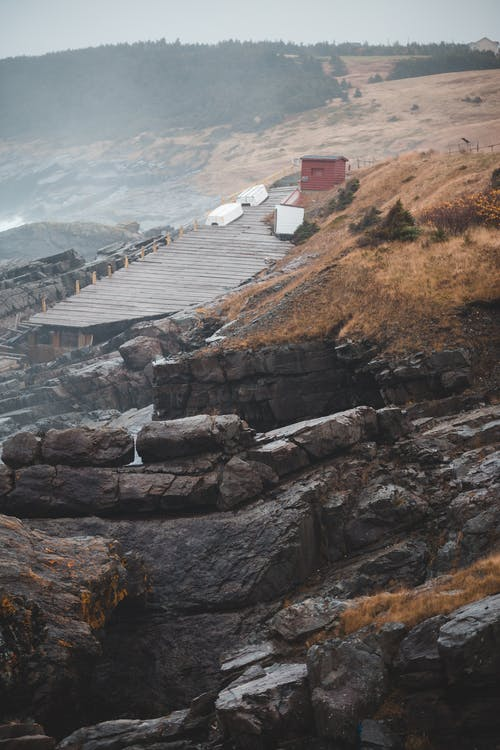 Damaged lumber road located on edge of rocky cliff on foggy gray day in mountains