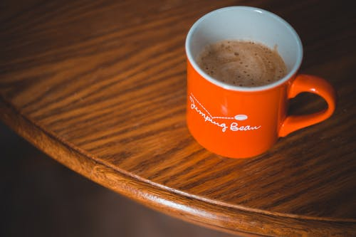 Orange Ceramic Mug on Brown Wooden Table