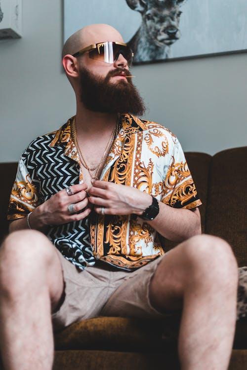 Man in Brown and Black Printed Shirt Sitting on Brown Sofa
