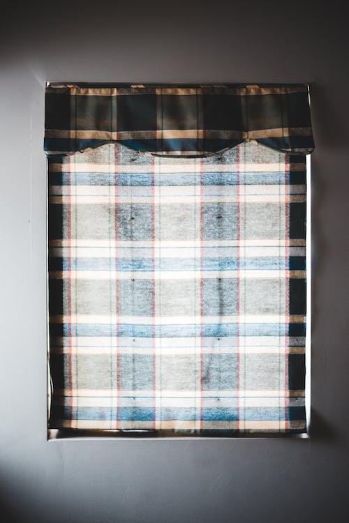 Tartan curtain on window in simple flat