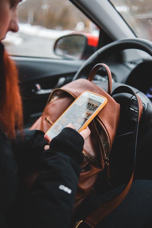 Female driver using smartphone in car