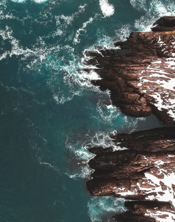 Drone view of majestic white ocean waves dashing against rocky cliffs in snow