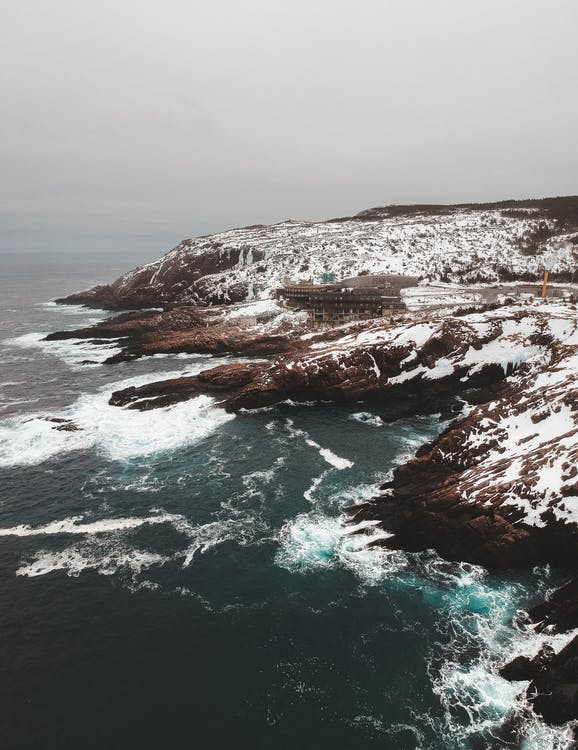 Aerial view of rocky cliffs in white snow washed with powerful ocean waves in haze