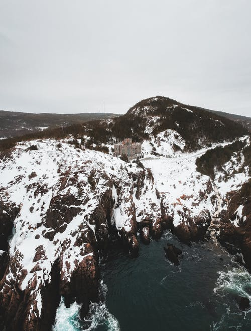 Aerial landscape of remote resort building in snowy valley with sea bay below in cold day