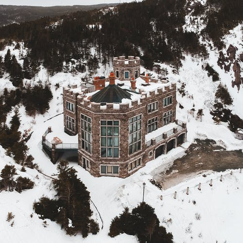 Aerial view of aged castle resort among evergreen woods on cold terrain in winter
