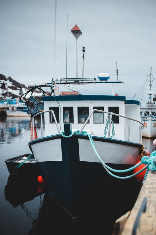 Modern fishing ship moored at wooden pier of coastal village under gloomy cloudy day